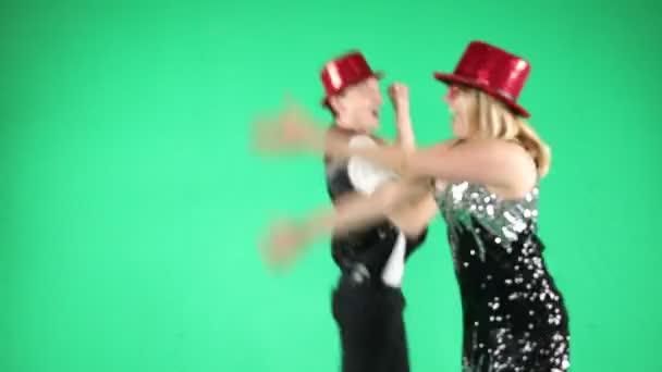 Aktivní srandovní mladý pár tančící skákání a směje se s legrační gesto na zelené barvy pozadí. Video záznam. Pošetilý blázen radostné náladě