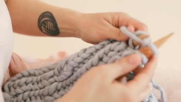 Maglia nelle vicinanze. Mani di sottofondo dei womans con tatuaggio fresco. Riprese video