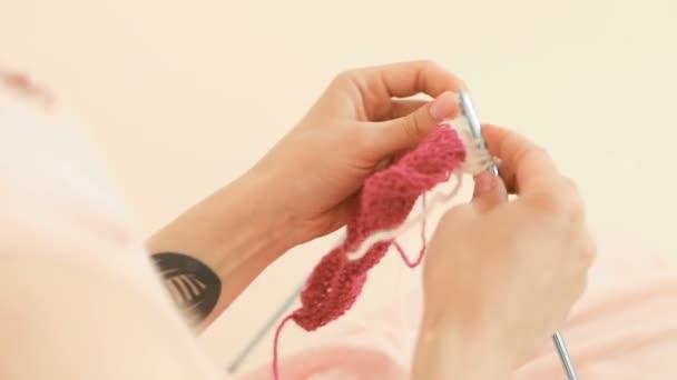 Bella luce riprese video del processo di lavoro a maglia. Donna bella mani della holding ferri da maglia e groviglio con discussioni