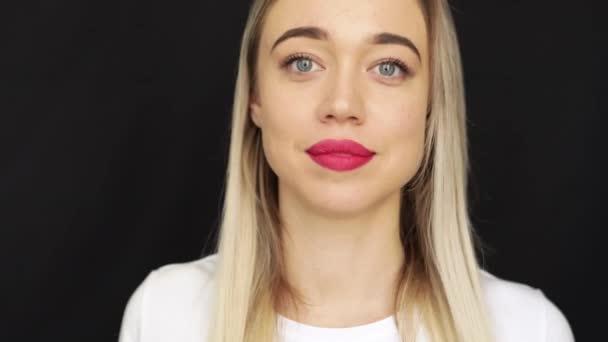 krásná blondýnka s červenými rty a modrýma očima. emocionální dlouhý pohled. Video záběry