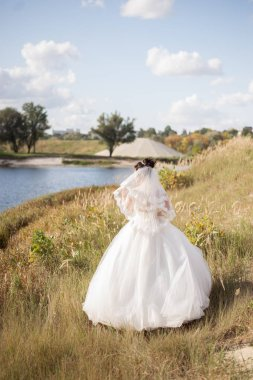 Stylish bride standing back with wedding bouquet on beautiful landscape of sea and mountains on sunset