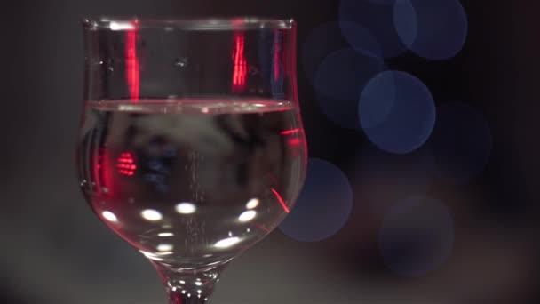 sklenice šampaňského s bublinkami, ozářená červeným světlem, stojí oslnivě, blikající světélka, v pozadí.