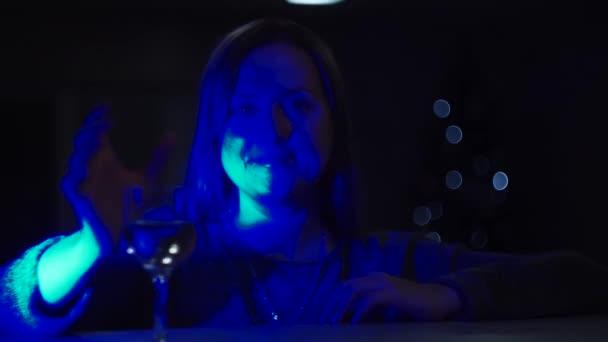 ein Mädchen in dunkelblauem Licht, mit leuchtendem Gesicht, trinkt Wein aus einem Glas