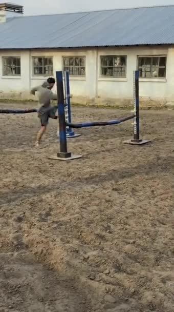 A fickó edz, átugrik akadályokon a faluban, a farmon.