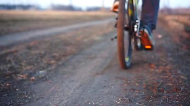 Zblízka. Muž jede kolo na spuštění pro trénink cvičit. Čas západu slunce.