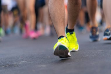 Marathon running people feet on road in the light at dawn