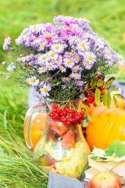 Arrangement of flowers and pumpkins in the meadow