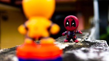 Selangor , Malaysia - March 28, 2019: Two McDonald's toy Deadpool and orange spiderman having a final fight on the road.