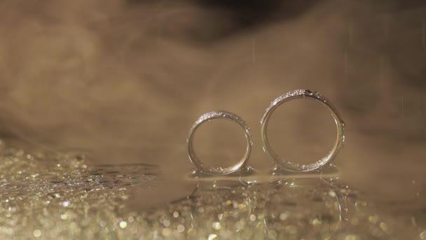 Svatební prsteny na tmavé vodní hladině zářící světlem. Kapky vody. Zavřít