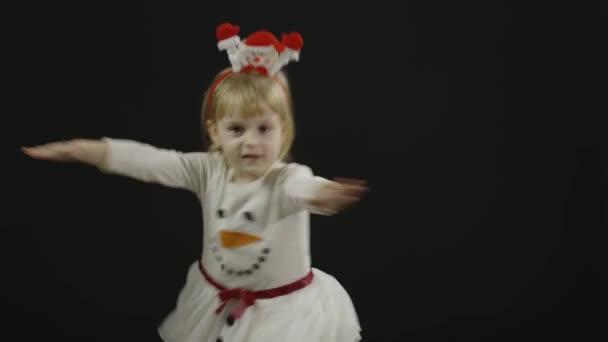 Šťastná krásná holčička ve sněhuláckém kostýmu. Vánoce. Udělej obličeje, tancuj