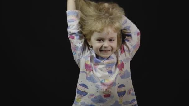 Das kleine Mädchen im Pyjama albert herum und macht Gesichter. schwarzer Hintergrund