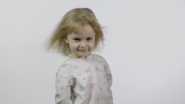 kleines hübsches Mädchen im Pyjama, das in die Kamera schaut. weißer Hintergrund