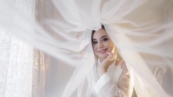 Gyönyörű és bájos menyasszony hálóingben a fátyol alatt. Esküvő napja