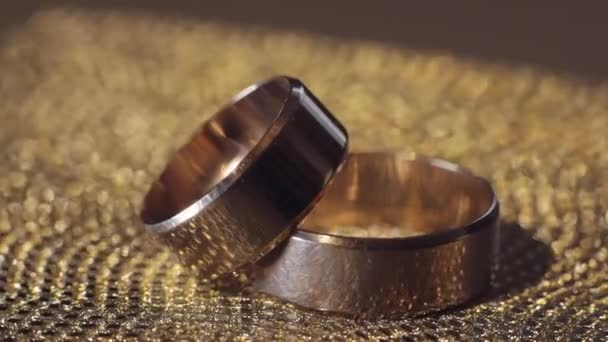 Wedding gold rings lying on shiny glossy surface. Shining with light. Close-up