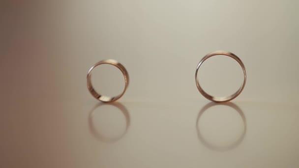 Svatební zlaté prsteny se válejí k sobě. Detailní záběr, makro