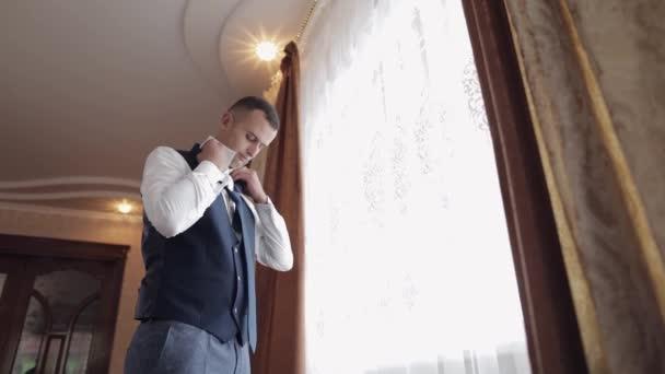 Ženich mu dá kravatu na krk. Připravuji se jít za nevěstou. Svatební den