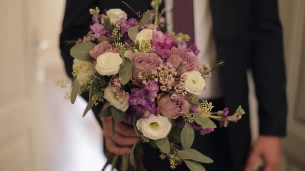 Groom with wedding bouquet in his hands. White shirt, jacket
