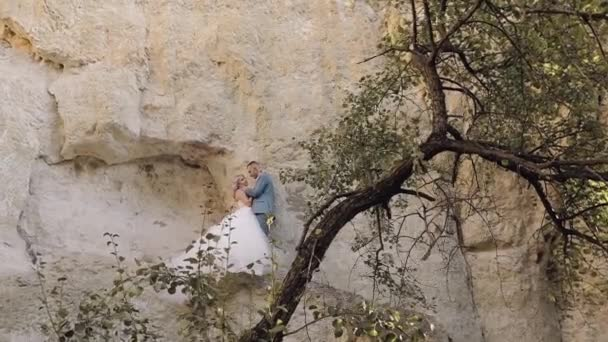 Wedding couple standing together on a mountainside. Newlyweds. Groom and bride