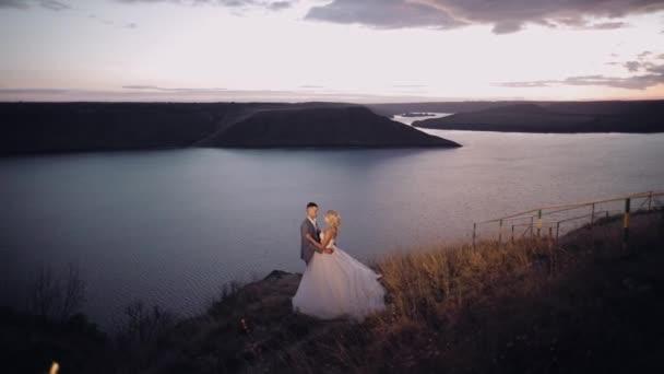 Novomanželé na horách u řeky. Západ slunce. Ženich a nevěsta