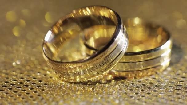 Svatební zlaté prsteny ležící na lesklém lesklém povrchu. Září světlem. Detailní záběr