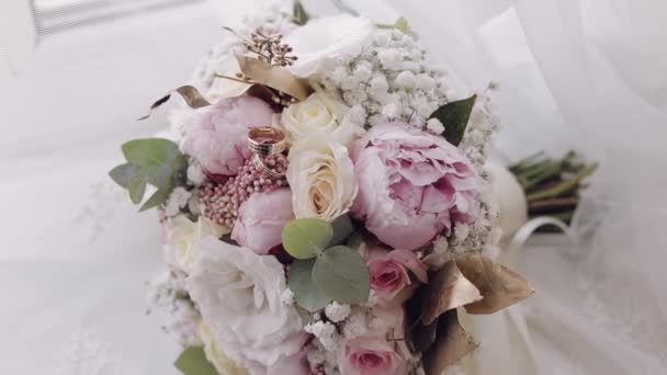 Beautiful wedding bouquet lie with wedding rings near window on white curtains