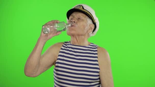 Elderly sailor man with mustache drinks vodka. Old sailorman on chroma key