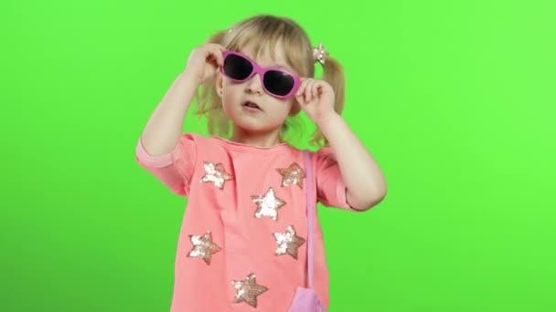 Pozitív lány rózsaszín blúzban és napszemüvegben táncol és pózol. Kroma kulcs