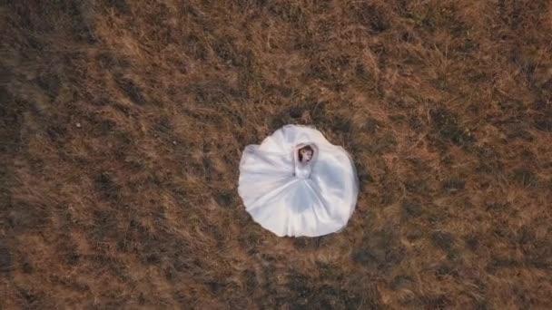 Gyönyörű és szép menyasszony menyasszonyi ruhában fekszik a füvön a pályán. Légi felvétel