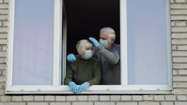 Old grandparents stay at window isolated at home on quarantine. Coronavirus