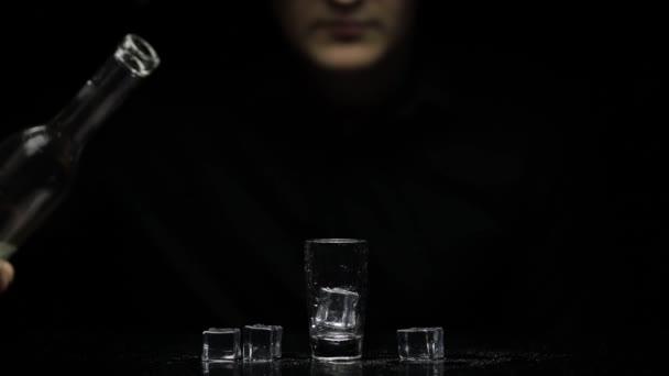 Barman nalít zmrzlou vodku z láhve do sklenice s ledem a vzít