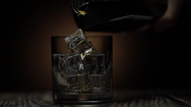 Whiskey-t, konyakot öntök az üvegbe. Sötét háttér. Alkoholtartalmú ital öntése