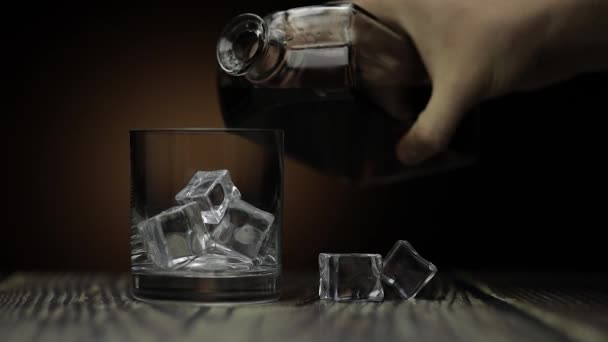 Whiskey, Cognac ins Glas gießen. Dunkler Hintergrund. Viel Alkohol getrunken