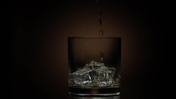 Nalít whisky, koňak do skla. Tmavé pozadí. Pour of alcohol drink