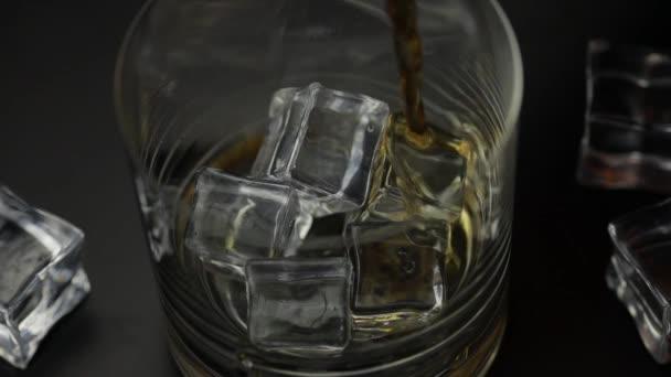 Nalít whisky, koňak do sklenice s kostkami ledu. Pour of alcohol drink