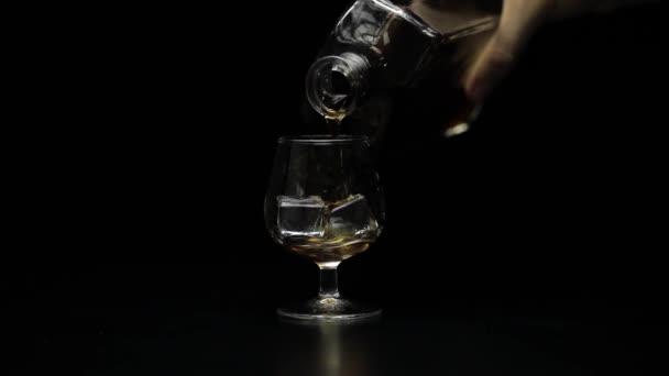 Alkoholos whiskyt, konyakot öntök az üvegbe. Fekete háttér. Lassú mozgás.