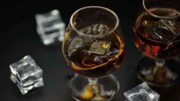 Kostka ledu spadla do sklenice whisky s alkoholem a koňakem. Zpomalený pohyb