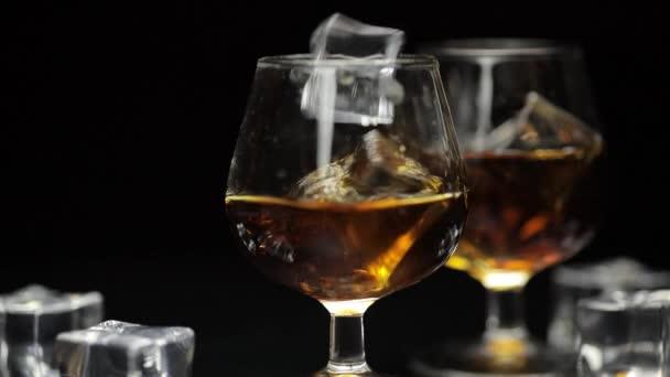 Jégkockákat dobtak egy pohár alkoholos whiskybe, konyakba. Lassú mozgás.