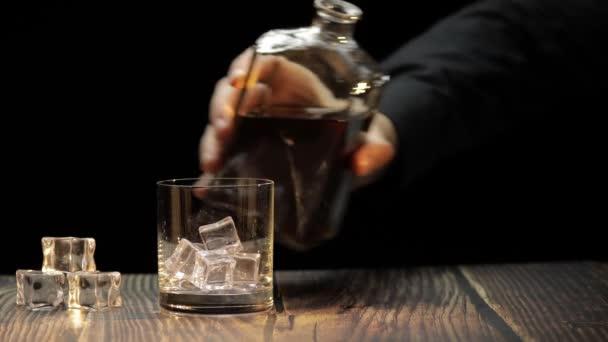 Nalít whisky, koňak do skla. Černé pozadí. Pour of alcohol drink