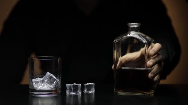 Nalít whisky, koňak do skla. Barman nalévá alkohol. Silueta