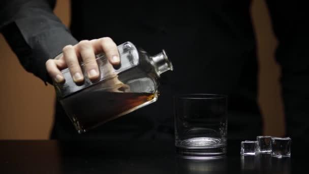 Nalít whisky, koňak do sklenice s kostkami ledu. Barman nalévá alkohol