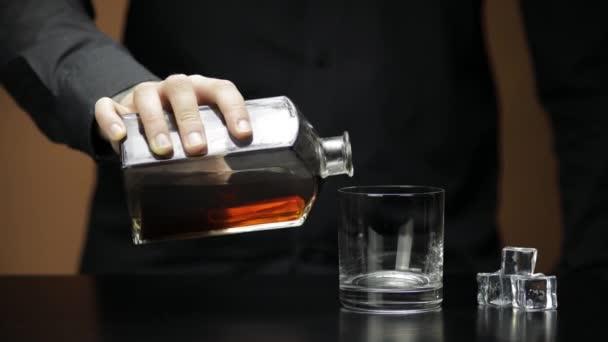 Whiskey-t öntök, konyakot jégkockákkal teli üvegbe. A csapos alkoholt önt.