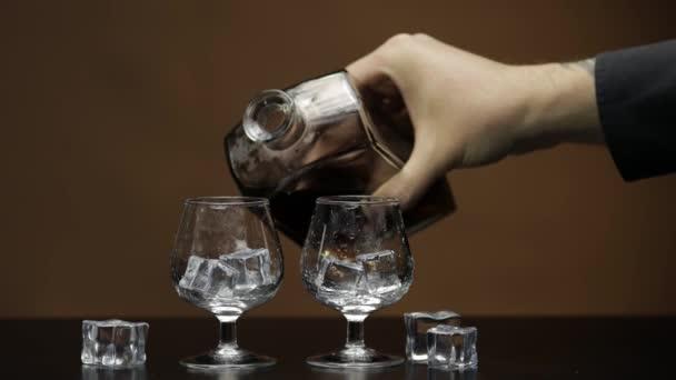 Nalít whisky, koňak do skla. Hnědá pozadí. Pour of alcohol drink