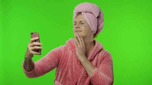 Portrét transsexuálního muže v županu vyrábějícího selfie pomocí mobilního telefonu