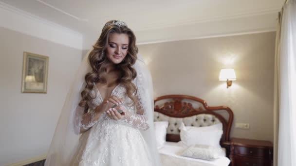 Krásná, krásná nevěsta ve svatebních luxusních šatech, závoj. Svatební kytice v rukou