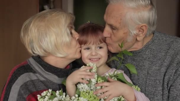 Grandfather and grandmother kissing on head their kid granddaughter at home