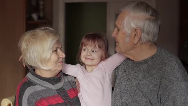 Smiling family grandfather, grandmother with child granddaughter at home
