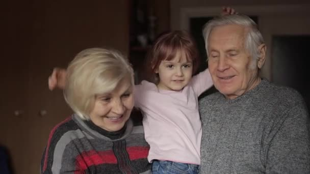 Granddaughter embraces senior smiling grandfather with grandmother at home
