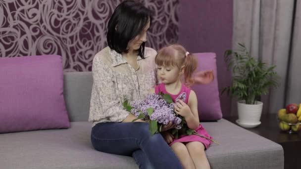 Little daughter and mother sitting on sofe with bouquet of lilac purple flowers