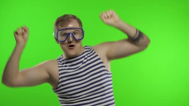 Emotionaler Mann in Unterwassermaske, gestreiftes Matrosenhemd tanzt und feiert