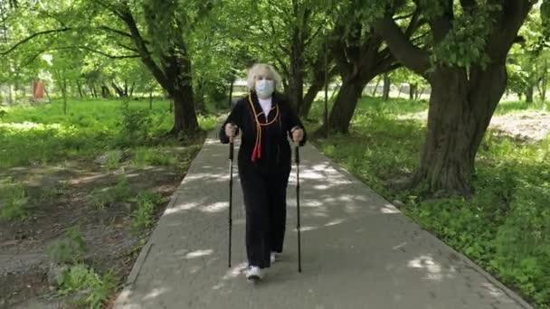 Aktive Seniorin beim Maskentraining Nordic Walking im Park unter Quarantäne